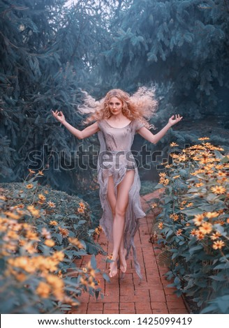 A renaissance country girl caring for a garden, the love of flowers returns her soul and she flies from happiness. The young healer, good forest witch. Photos of levitation and soaring in the air.