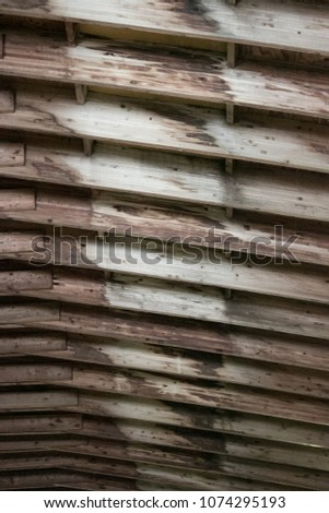 A repetitive pattern of arched wooden girders in the roof of a buidling. #1074295193