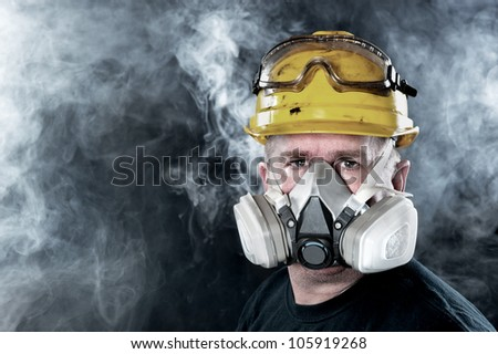 A rescue worker wears a respirator in a smokey, toxic atmosphere.  Image show the importance of protection readiness and safety. - stock photo
