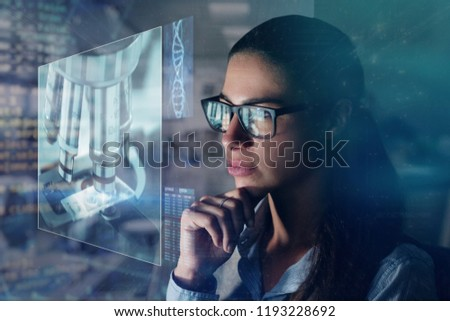 A research scientist analyzes the DNA of a patient under a microscope. The researcher uses a futuristic holographic monitor. Concept of: science, research and development, technology and future.