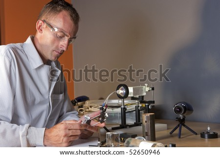 A researcher in a lab coat studying a piece of equipment for an experiment. He is wearing safety glasses. Horizontal shot.