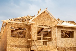 A residential frame house construction project showing the engineered truss roof rafters and oriented strand chip board engineered wall sheathing