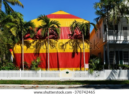 A residential house covered with a red and yellow canvas tent while being fumigated for termites.
