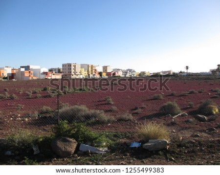 A residential neighborhood in the outskirts of Las Palmas on the Spanish Island of Gran Canaria in the Atlantic Ocean. The picture shows undeveloped barren wasteland with scattered brush and gravel.