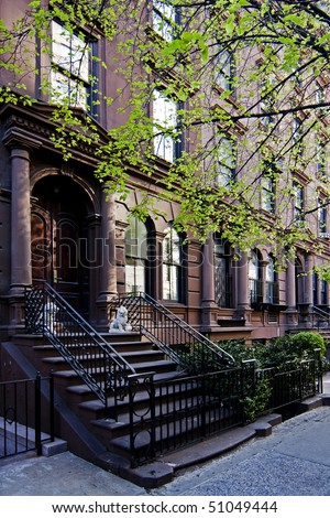 A residential New York, Philadelphia, Boston or Chicago brownstone townhouse building with balck fence and steps in front.