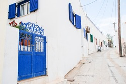 A residential street in traditional white and blue Fira village in Santorini, Greece