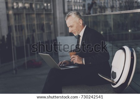 A respectable old man in a strict business suit sits on the parapet of the building and works behind a laptop. Next to him is his mono-wheel #730242541