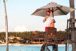A responsible lifeguard man stands on a tower and is ready to save tourists bathing in the water.