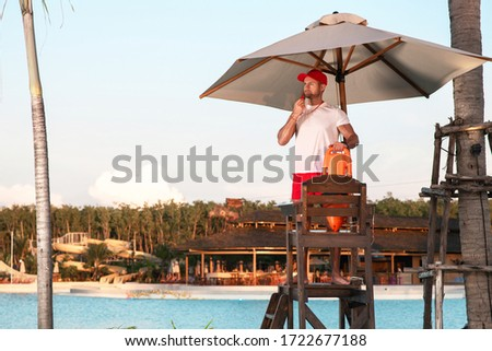 A responsible lifeguard man stands on a tower and is ready to save tourists bathing in the water. Stockfoto ©