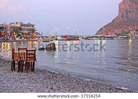 A restaurant table and chairs by the sea of Monemvasia, Greece (focus is on the table/chairs)