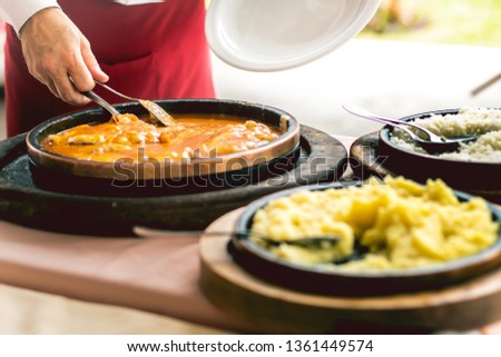 A restaurant waiter serving the food. On the table the food is chicken parmigiana ( Parmegiana de frango ), boiled rice and mashed potatoes. Stockfoto ©