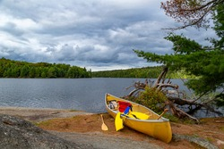 A resting yellow canoe, with life jackets, on the rocky shores of a beautiful small island at Algonquin Park, Ontario, Canada