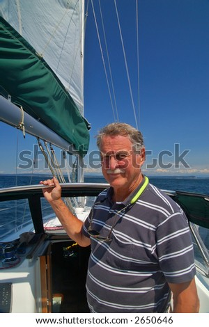 A retired man on his sailboat posing for a photo