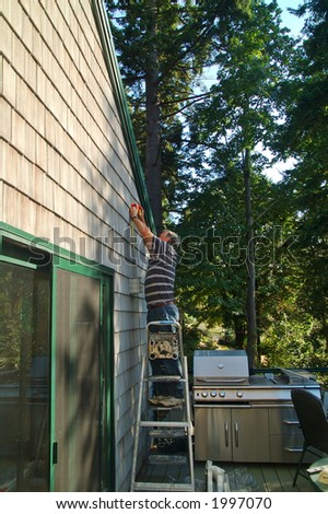 A retired man putting up an awning on the sliding glass door