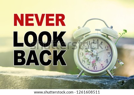 A retro alarm clock in the morning light with nature background. A text 'Never Look Back' written on image.