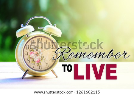 A retro alarm clock on a white table top with nature background and morning sunlight. A text 'Remember to live' written on image.