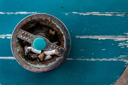 A retro, antique cigarette ashtray filled with stubs on a turquoise sanded wooden table top.