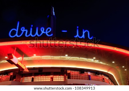 A retro diner all lit up at night with bright neon signage