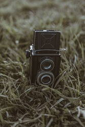 A retro film camera standing on a green grass. Close-up of an old photocamera in summertime.  A soviet medium format dual lens mirror camera. Lomography effect. A Vintage, authentic, hipster copcept
