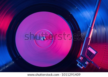 A retro-styled spinning record vinyl player. Vintage shot of old gramophone, playing close up. Beautiful colorful movie. Neon violet led light.