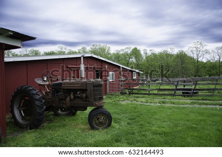 A retro tractor parked next to a barn in a farm at Jobstown, NJ.