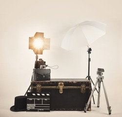 A retro vintage camera with studio lights and various photography lighting equipment for a director or film concept.