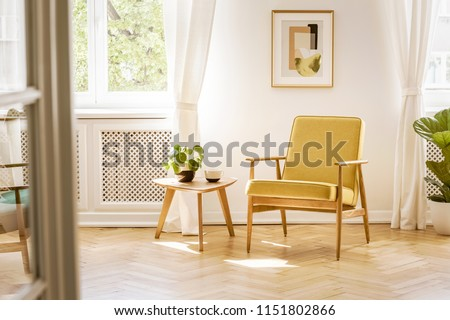 A retro, yellow armchair and a wooden table in a beautiful, sunny living room interior with herringbone floor and white walls. Real photo.