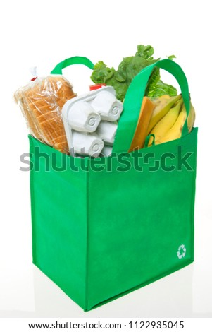 A reusable grocery bag with recycle symbol, filled with basic groceries. #1122935045