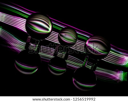 A ribbon of colors decorate the multiple orbs in the foreground. #1256519992