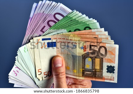 A rich man hand shows thousands of Euros in 50 euro 100 euro and 500 euro banknotes on a blue background. wealth concept, concept of wealth