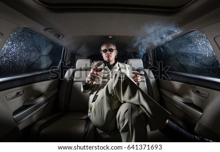 A rich man in a white suit and a cigar with a glass of wine in the car, a limousine #641371693