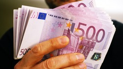 a rich man shows 10,000 euros in many 500 euro notes. Concept of wealth and richness