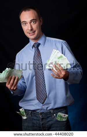 A rich man shows his earnings with an expression of success. Wads of money in his hands and pockets.Conceptual image for business success, rich people, income, ...