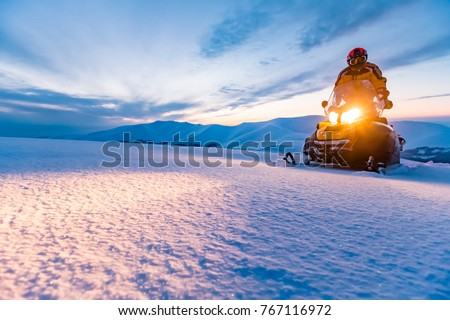 A rider on the snowmobile. Beautiful winter day in Ukrainian mountains. Sunset. - Shutterstock ID 767116972