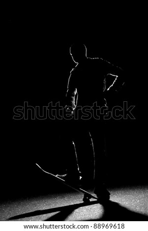 A rim lit skateboarder guy posing under dramatic back lighting with his skateboard flipped up in the front.