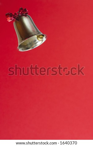 A ringing bell, decorated with a red ribbon. on bright re background, Space for text.