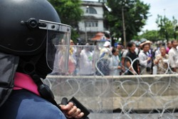 A Riot Police Officer Stands Guard During a Political Protest