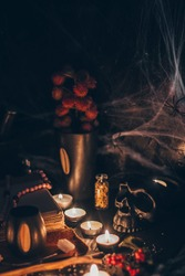 A ritual halloween witchcraft scene with candles, herbs, spider web, vintage bottles on the rustic background with a scary skull face and antique book.