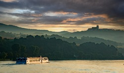 A river cruise boat on the Danube river at sunset, in the Melk District, lower Austria near Sausenstein
