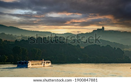 A river cruise boat on the Danube river at sunset, in the Melk District, lower Austria near Sausenstein Сток-фото ©