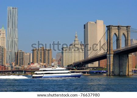 A river cruise boat on the East River heading under the Brooklyn Bridge in New York City.