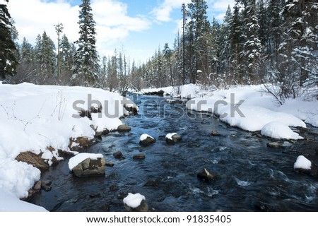 A river in the mountains with snow along the banks.