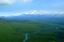 A river is winding among pristine woods with a backdrop of snowcapped mountains in Kamchatka, Russia