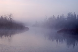 A river on a foggy morning at sunrise