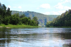 A river that flows through the forest. Mountain forest in the distance in a blue haze, river water landscape, sunny blue sky, Russia, South Ural, Belaya river, river rafting, travel.
