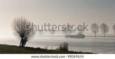 A river with trees on the banks in early morning mist. A foggy landscape in the Netherlands.