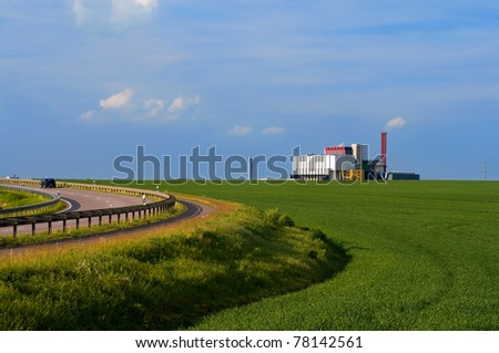 A road bend by green fields with a factory on the horizon