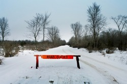 A road closed barricade on a snow covered country road.