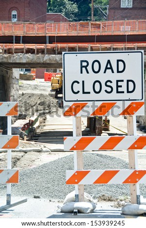 A road closed sign blocks off traffic from a construction site under a crumbling bridge.