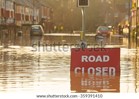 A \'Road Closed\' sign partially covered in flood water lit by the evening sun